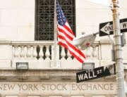A Wall Street road sign is pictured in front of an entrance to the New York Stock Exchange in the financial district of New York September 19, 2008. Sweeping government measures to rescue the financial system and restore confidence in shaky markets spurred a huge relief rally in U.S. stocks on Friday, ending a week that saw the most dramatic reshaping of the financial landscape since the Great Depression. REUTERS/Lucas Jackson (UNITED STATES)